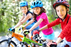 Children on bicycles wearing helmets.