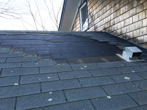 Roof with wind damage, missing shingles.