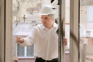 Insurance adjuster inspecting damaged home