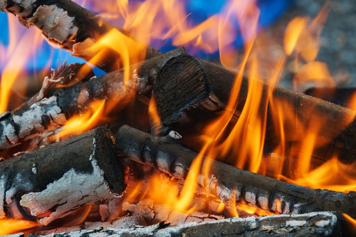 Three flaming logs in a wood-burning stove