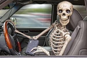 A skeleton behind the wheel of an SUV, distracted by his cell phone. He is also not wearing a seatbelt.