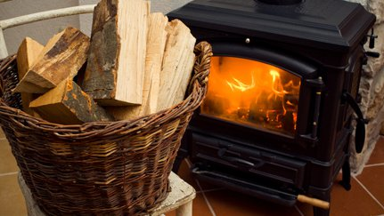 A fire in a wood-burning stove with basket of firewood.